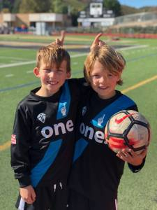 two players posing with soccer ball